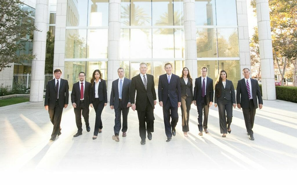 injury attorneys torrance ca group photo 10 people in black suits yellow